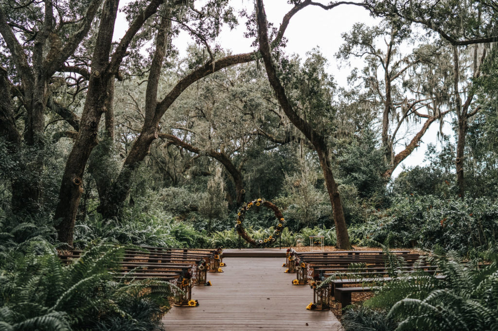Rustic Dover Burgundy and Yellow Sunflower Outdoor Wedding Ceremony with Wood Benches and Round Grapevine Branch Arch and Lanterns down the Aisle