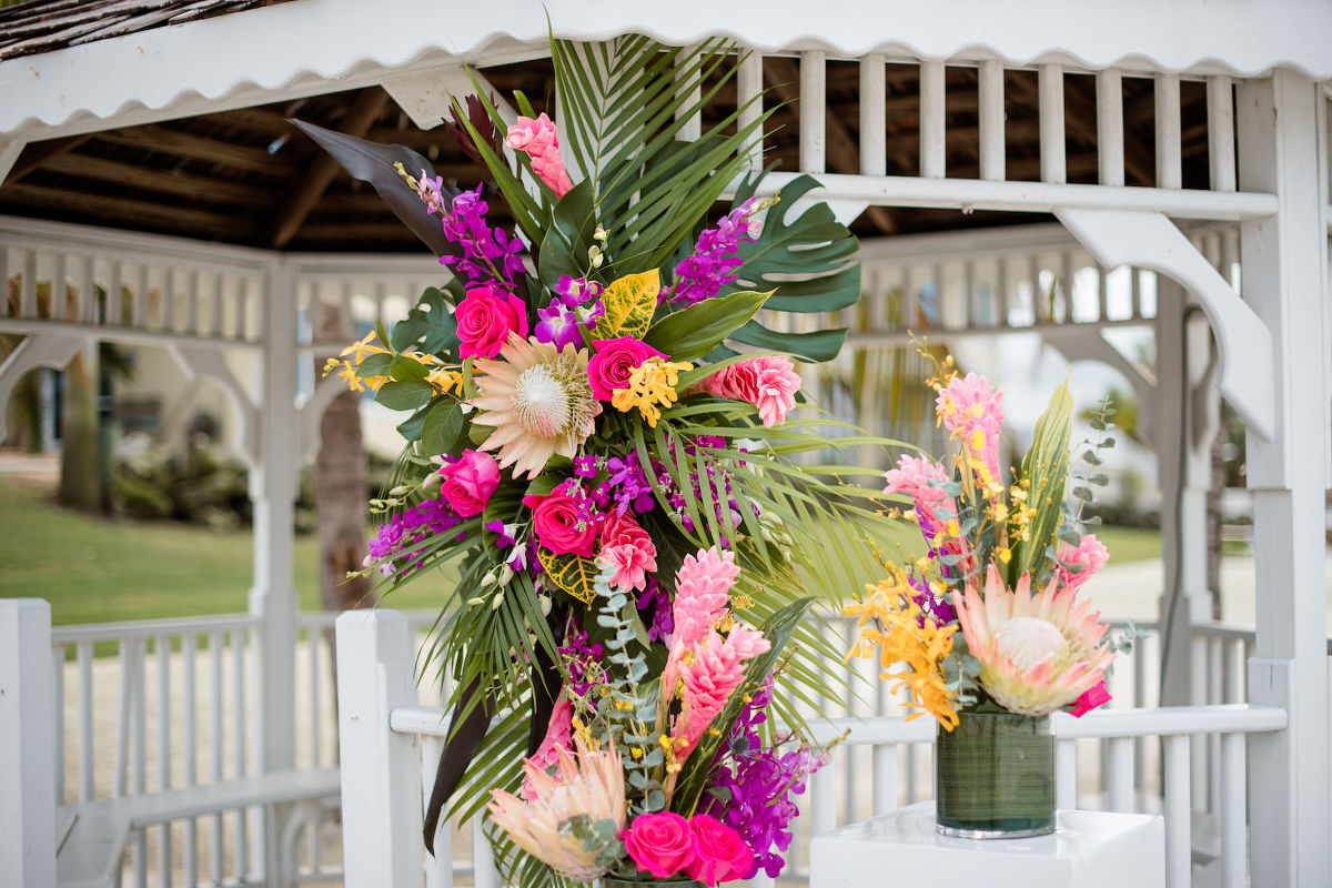 Tropical Florida Wedding Ceremony Decor, Alter Floral Arrangement, Bright Pink Exotic Flowers, Purple Stems, Blush King Proteas, with Green Palms and Monstera Leafs | Tampa Bay Vow Renewal and Microwedding Planner Perfecting The Plan | St. Petersburg Private Beachfront Venue Isla Del Sol