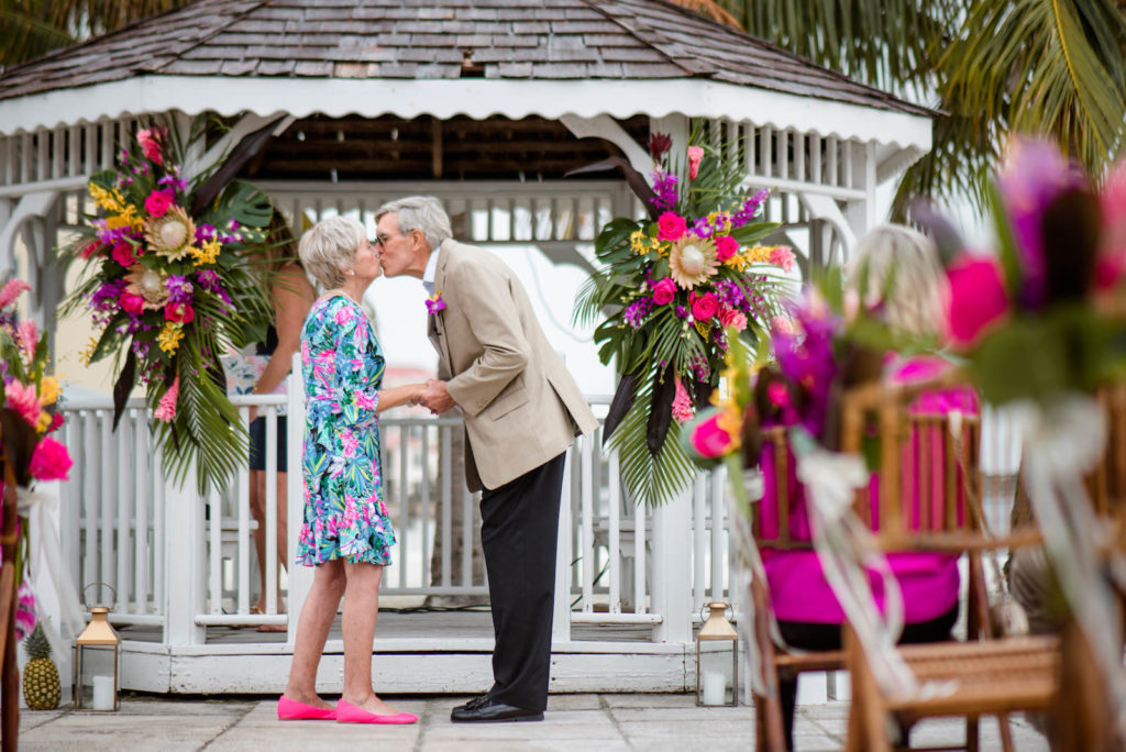 Florida Husband and Wife Kiss at Tropical Wedding Vow Renewal Ceremony with Decor, Bamboo Folding Chairs, Lilly Pulitzer Themed Floral Arrangements, Gazebo Alter with Bright Pink Exotic Flowers, Purple Stems, Blush King Proteas, with Green Palms and Monstera Leafs | Tampa Bay Vow Renewal and Micro wedding Planner Perfecting The Plan | St. Petersburg Private Beachfront Venue Isla Del Sol | St. Pete Beach DJ Grant Hemond & Associates