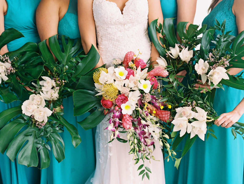 Tampa Bay Bride in Lace Wedding Dress with Bridesmaids in Mix and Match Teal Dresses Holding Tropical Floral Bouquets, Tropical Pink Ginger, Yellow Pincushion Protea, Purple Orchid, Greenery, Monstera Palm Tree Leaves Flowers