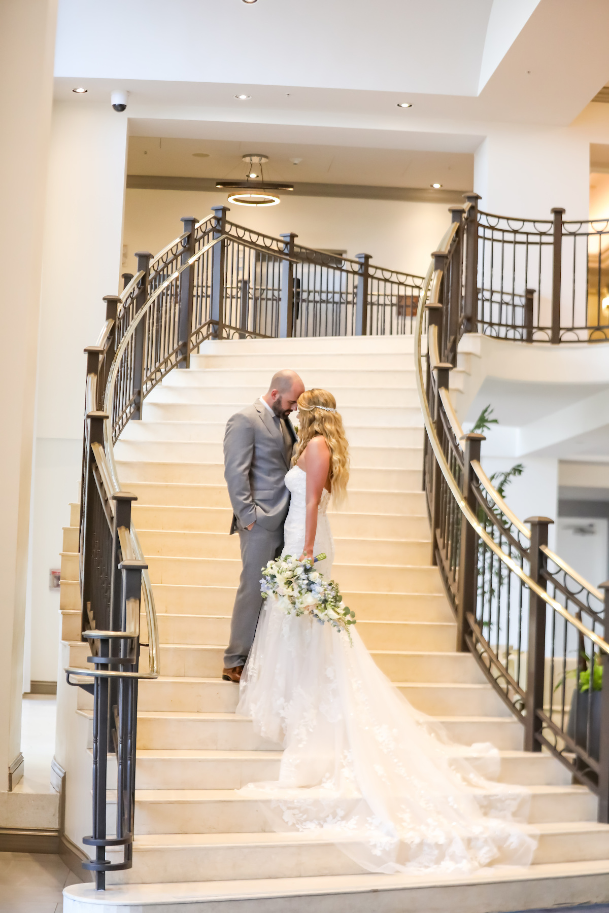 Indoor Bride and Groom Staircase Portrait at Clearwater Wedding Venue Hyatt Regency Clearwater Beach | Groom Wearing Silver Grey Suit | Strapless Lace Sweetheart Mermaid Wedding Dress Bridal Gown | Lifelong Photography Studio