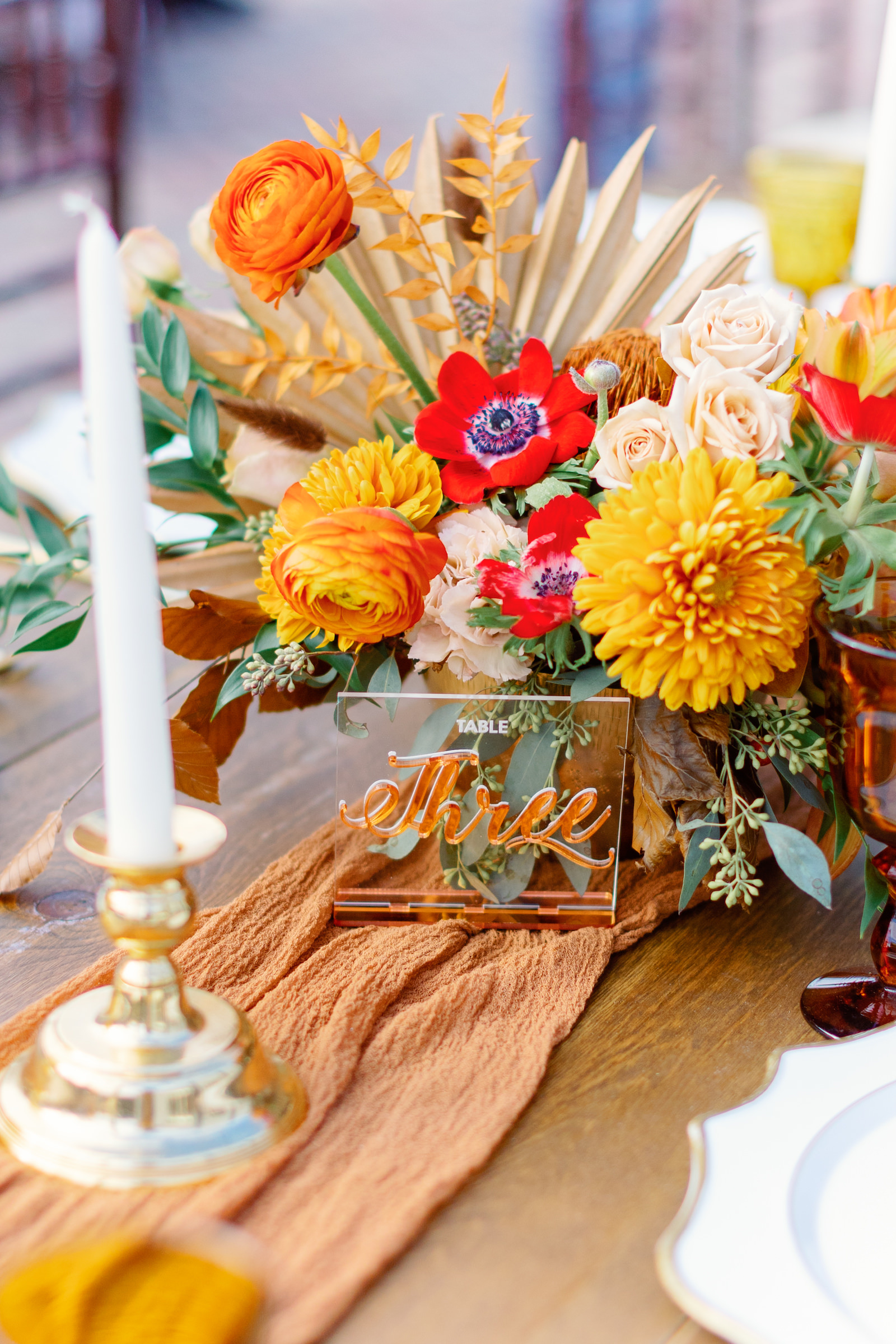 Modern Boho Inspired Florida Wedding Reception and Decor   Long Wooden Feasting Table with Orange Linen Table Runner with Long White Candles and Gold Candleholder, White Chargers, Acrylic Table Number, Yellow Drinking Goblets, Red Flowers, Marigolds Centerpiece   Tampa Bay Wedding Planner Coastal Coordinating