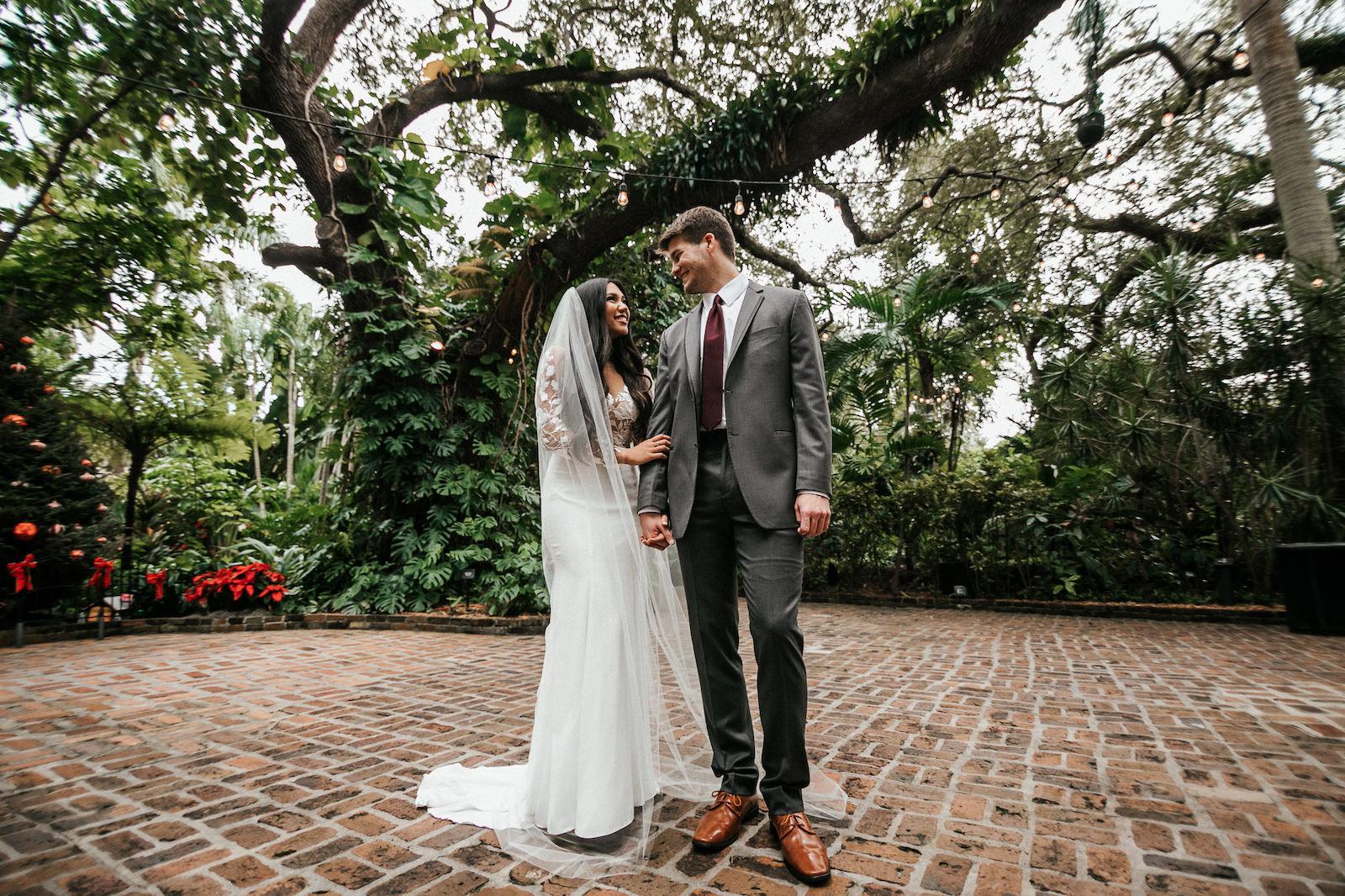 Tampa Bay Bride and Groom At Sunken Gardens Wedding Venue in St. Petersburg, Bride Wearing BHLDN Wedding Dress, Groom Wearing Wine Burgundy Color Tie and Charcoal Gray Suit | Florida Wedding Planner John Campbell Weddings