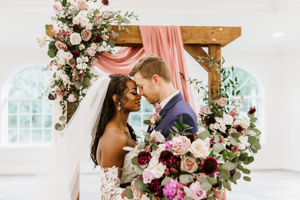 Bride and Groom Indoor Church Portrait at St. Pete Wedding Venue Harborside Chapel | Wood Arch with Draping and Natural Floral Arrangement Swag with Pink and White Roses and Eucalyptus Greenery | Lace and Tulle Ballgown Bridal Gown Wedding Dress with Illusion Lace Long Sleeves | Navy Groom Suit | Bridal Bouquet with Ivory Pink and Burgundy Maroon Roses with Eucalyptus Greenery and Cascading Pink Velvet Ribbons