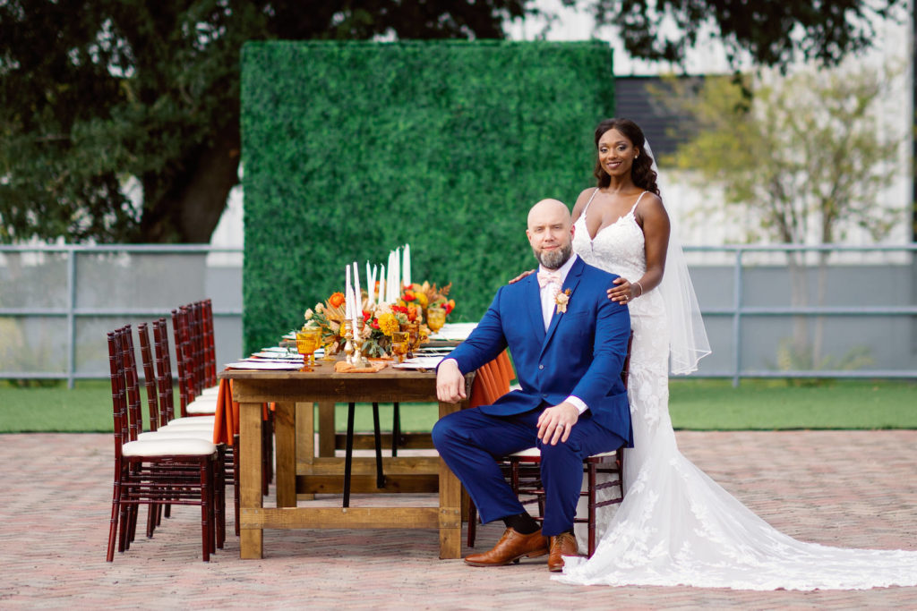 Downtown St. Petersburg Bride and Groom, Modern Boho Florida BrideWearing White Lace Mermaid Style Dress, Groom in Dark Blue Suit, Long Wooden Feasting Table with Vibrant Yellow and Red Floral Centerpiece, Tall White Candles and Gold Candlesticks, Wooden Chiavari Chairs, Greenery Wall Backdrop | Tampa Bay Wedding Planner Coastal Coordinating