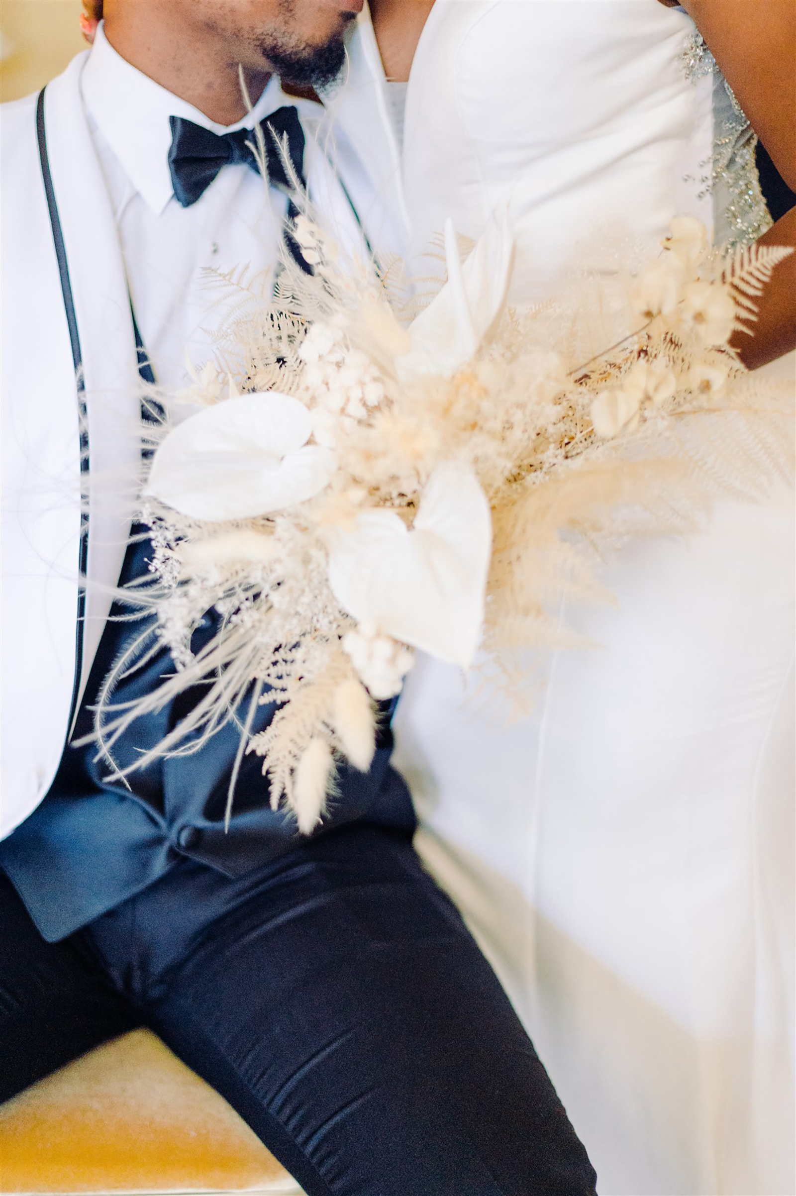 Modern and Boho Groom in White and Black Tuxedo, Bride in Classic Dress Holding Dried Unique White Floral, Feathers and Foliage Bouquet | Tampa Bay Wedding Planner, Designer, Florist John Campbell Weddings
