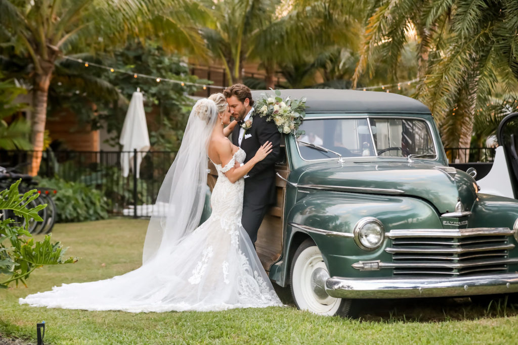 Elegant Sarasota Bride and Groom With Vintage Car at Anna Marie Island Courtyard Wedding | Bride Wearing White Fit and Flare Wedding Dress with Off the Shoulder Lace Sleeves, Holding Lush Ivory Floral Bouquet with Greenery, Groom in Classic Black Tuxedo | Florida Wedding Photographer Lifelong Photography Studio | Tampa Bay Wedding PlannerKelly Kennedy Weddings