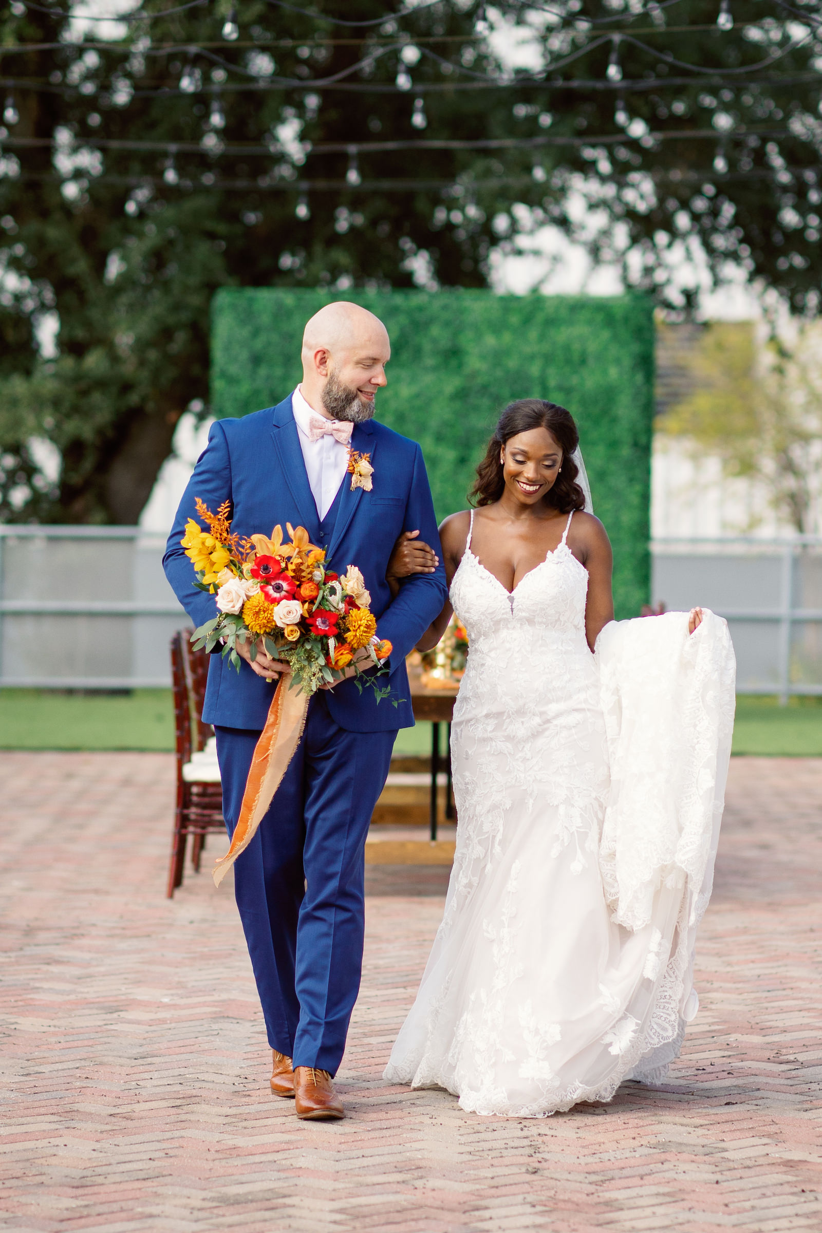 Downtown St. Petersburg Bride and Groom, Modern Boho Florida Bride Wearing White Lace Mermaid Style Dress, Groom in Dark Blue Suit Holding Vibrant Autumn-Inspired Floral Bouquet with Orange, Yellow, Red and White Florals   Tampa Bay Wedding Planner Coastal Coordinating