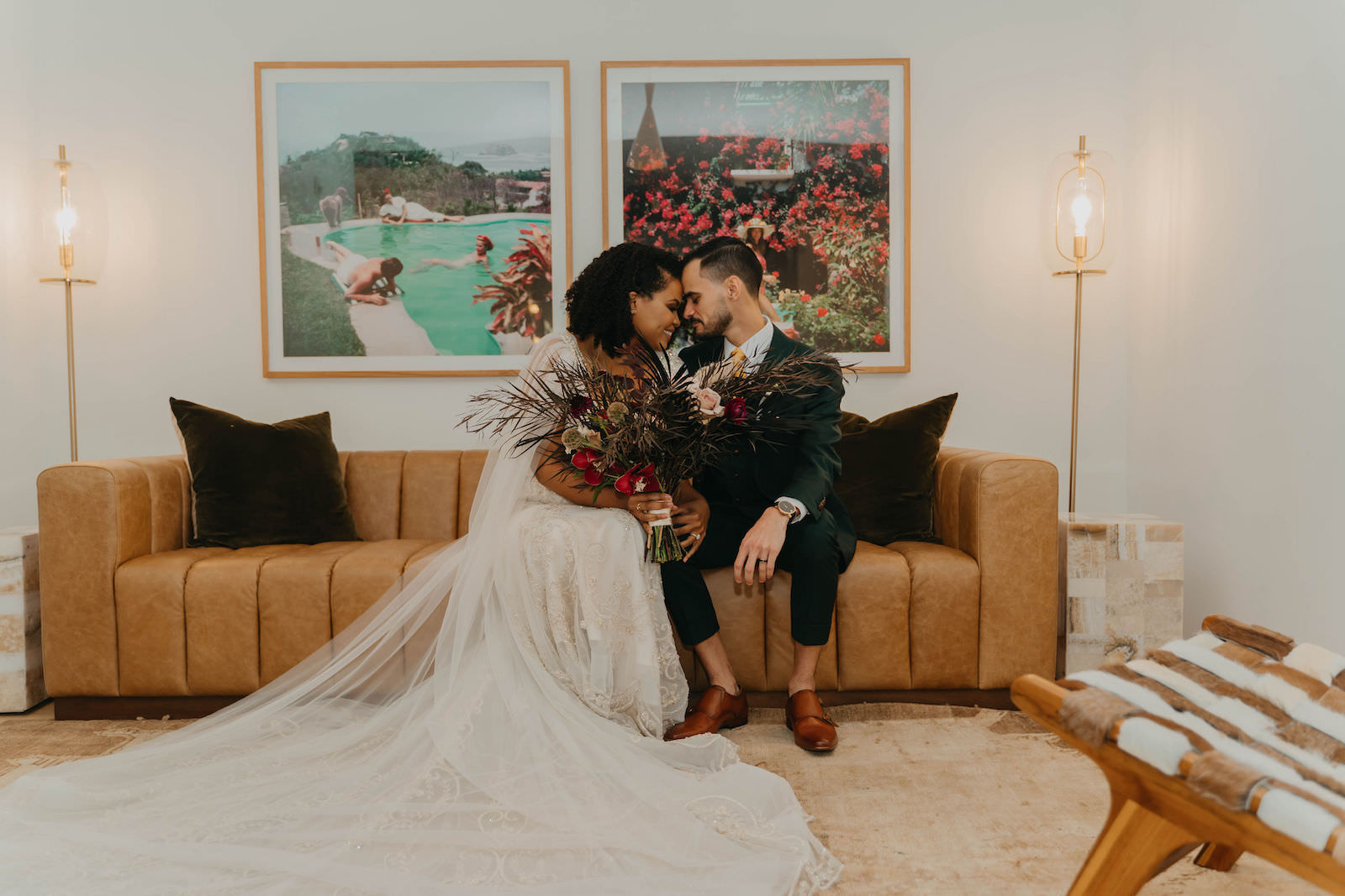 Indoor Bride and Groom Portrait in Tampa Wedding Venue Hyde House   Illusion Lace Embroidered Beaded V Neck Wedding Dress Bridal Gown with Sheer Tulle Cape Sleeves by Designer Amalia Carrara Bridal   Groom in Classic Black Tux Suit with Gold Tie   Loose Wild Boho Bridal Bouquet with Deep Red Burgundy and Blush Roses