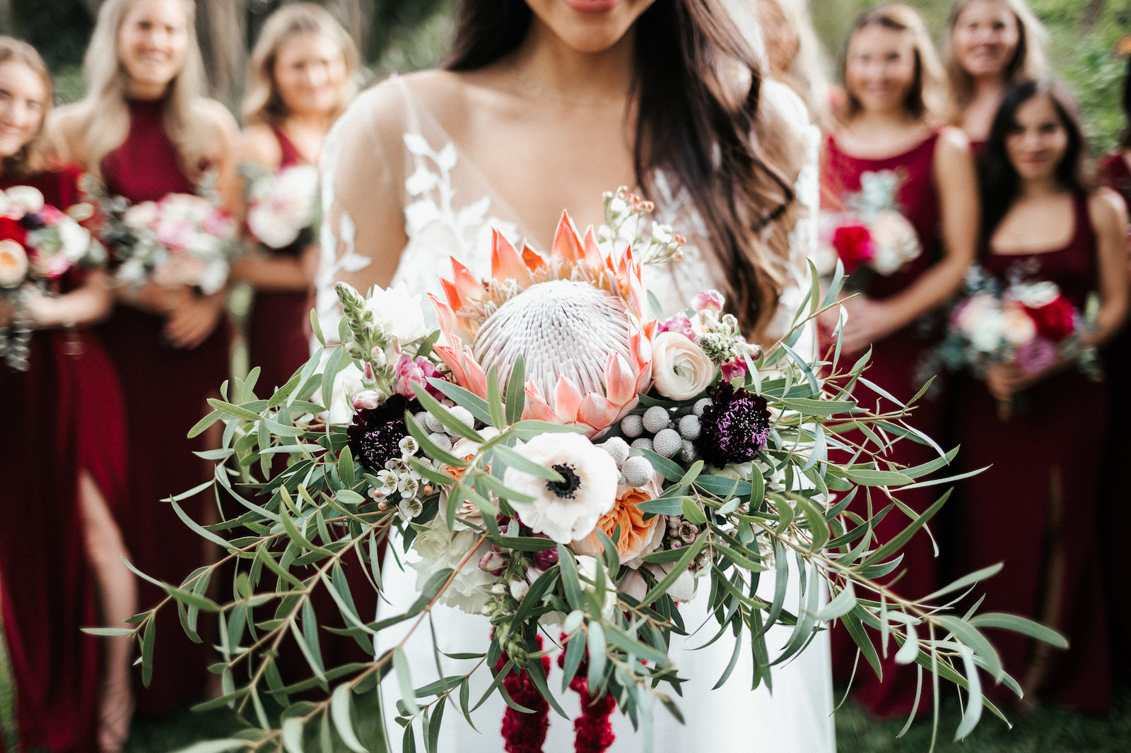 St. Petersburg Bride Holding Exotic Tropical Inspired Bridal Bouquet with Bright Pink King Protea, White, Dark Purple, Burgundy, Wine Florals with Greenery | Florida Wedding Florist Posies Flower Truck | Tampa Bay Wedding Planner John Campbell Weddings
