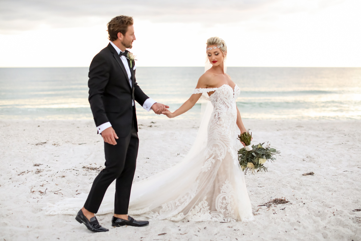 Elegant Sarasota Bride and Groom Walking on Anna Marie Island Beach at Sunset, Wearing Vintage Crystal Headpiece with White Fit and Flare Wedding Dress and Off the Shoulder Lace Sleeves, Holding Lush Ivory Floral Bouquet with Greenery, Groom in Classic Black Tuxedo | Florida Wedding Photographer Lifelong Photography Studio | Kelly Kennedy Weddings and Events