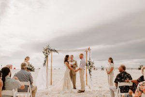 Beach Wedding Ceremony Venue at Hilton Clearwater Beach | White Folding Garden Chairs and Bamboo Arch with Sheer Draping and Greenery Floral Arrangement Tie Backs with White Roses