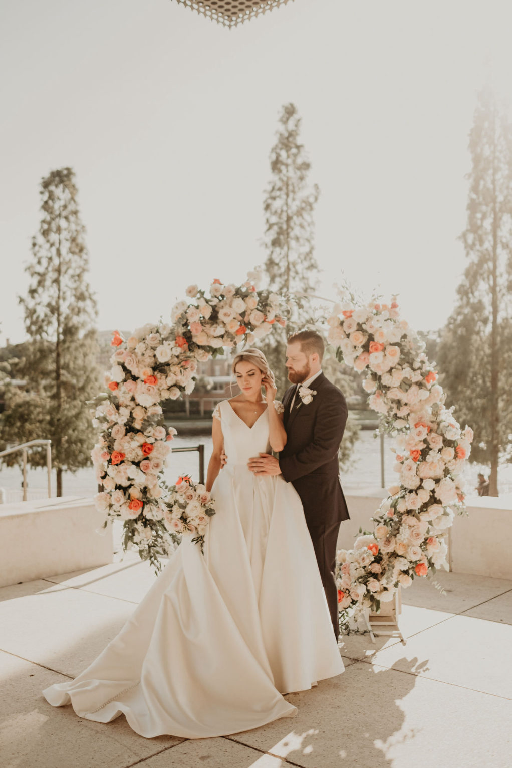 Outdoor Downtown Tampa Waterfront Bride and Groom Portrait with Round Arch Floral Arrangement with Peach Salmon Coral Roses White Hydrangea and Eucalyptus Greenery | V Neck Mikado Satin Ballgown Wedding Dress by Anomalie | Groom Wearing Classic Black Suit Tux