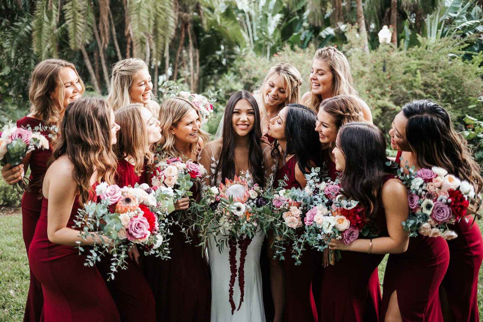 St. Petersburg Bride and Bridal Party, Holding Exotic Tropical Inspired Bridal Bouquet with Bright Pink King Protea, White, Dark Purple, Burgundy, Wine Florals with Greenery, Bridesmaids in Long Mismatched BHLDN Dresses in Dark Burgundy and Wine Color | Florida Wedding Florist Posies Flower Truck | Tampa Bay Wedding Planner John Campbell Weddings