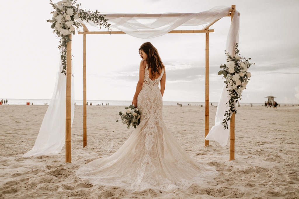 Beach Wedding Ceremony Venue at Hilton Clearwater Beach | White Folding Garden Chairs and Bamboo Arch with Sheer Draping and Greenery Floral Arrangement Tie Backs with White Roses Chrysanthemums and Stock | Allure Bridals Lace Low Back Spaghetti Strap Sheath Bridal Gown Wedding Dress