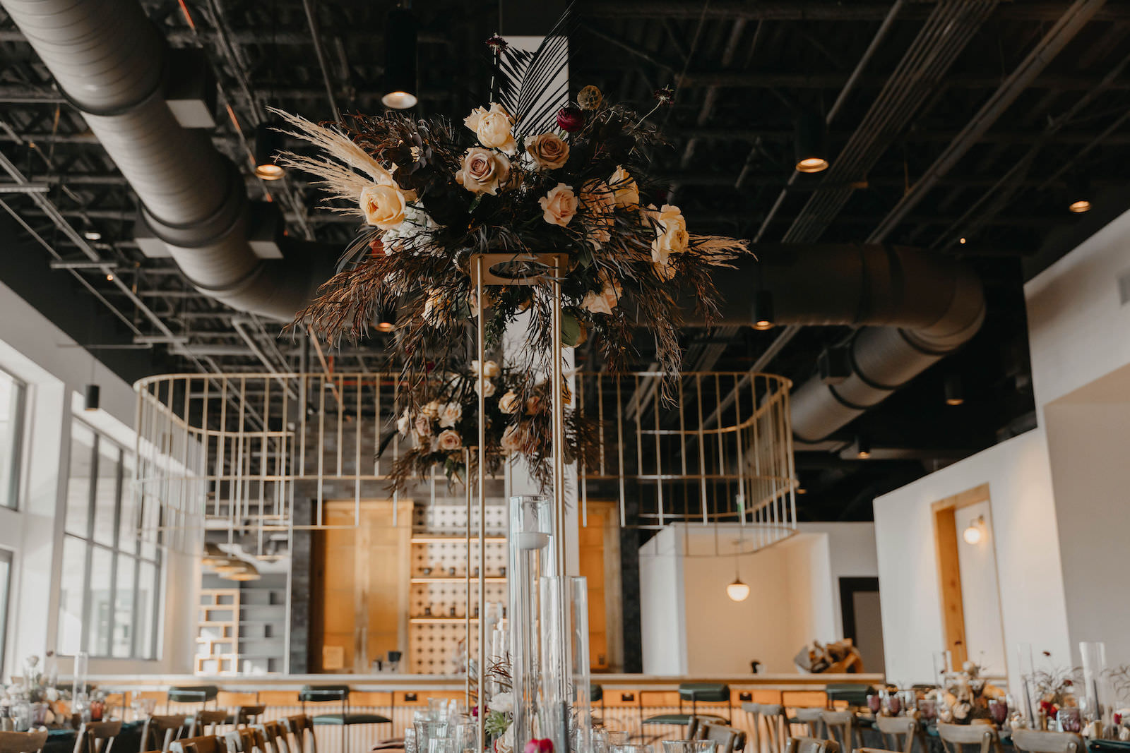 Indoor Wedding Reception at Tampa Wedding Venue Hyde House   Tall Geometric Vase Centerpieces with Dark Green and Black Leaves, Pampas Grass, and Blush Cafe au Lait Roses with Candlesticks