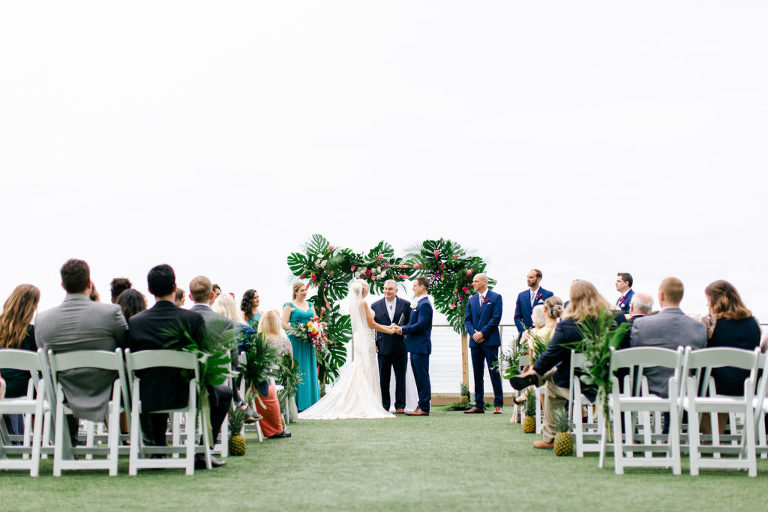 Tropical Elegant Wedding Ceremony, Bride and Groom Exchanging Vows Under Arch with Monstera Palm Tree Leaves, Pink Ginger Florals | Tampa Bay Wedding Planner Special Moments Event Planning | Clearwater Beach Opal Sands Resort