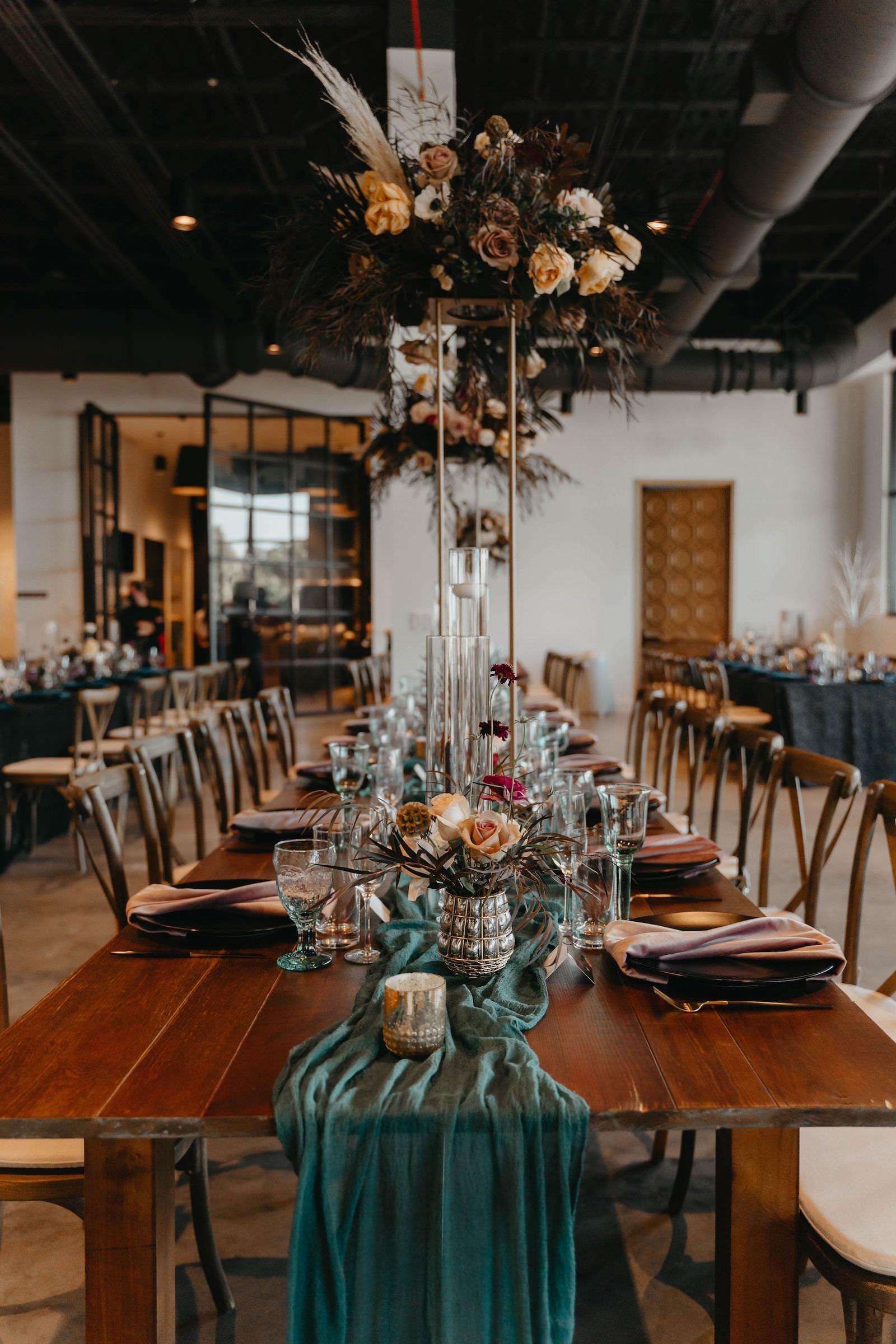 Indoor Wedding Reception at Tampa Wedding Venue Hyde House   Long Wood Feasting Communal Tables with Cross Back Chairs and Dark Emerald Green Cheesecloth Gossamer Runners   Tall Geometric Vase Centerpieces with Dark Green and Black Leaves, Pampas Grass, and Blush Cafe au Lait Roses with Candlesticks