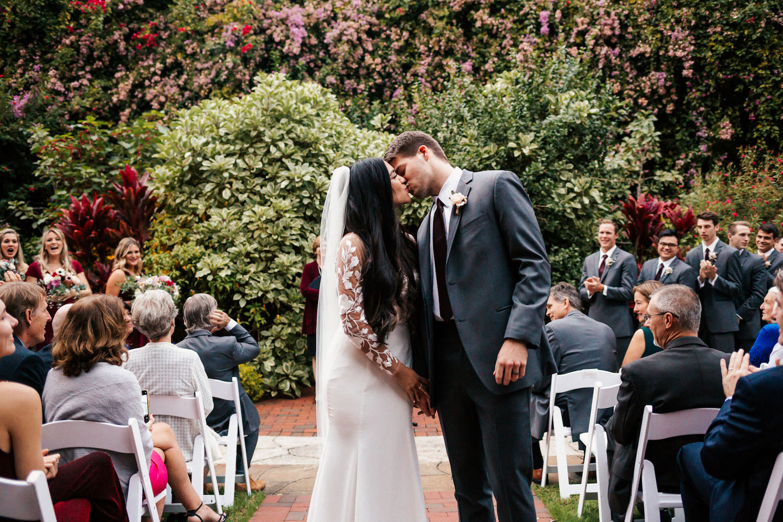 Tampa Bay Bride and Groom Kiss At The End of The Aisle At Sunken Gardens Wedding Ceremony, Bride Wearing Long White BHLDN Wedding Dress with Illusion Lace Sleeves | Florida Wedding Planner John Campbell Weddings