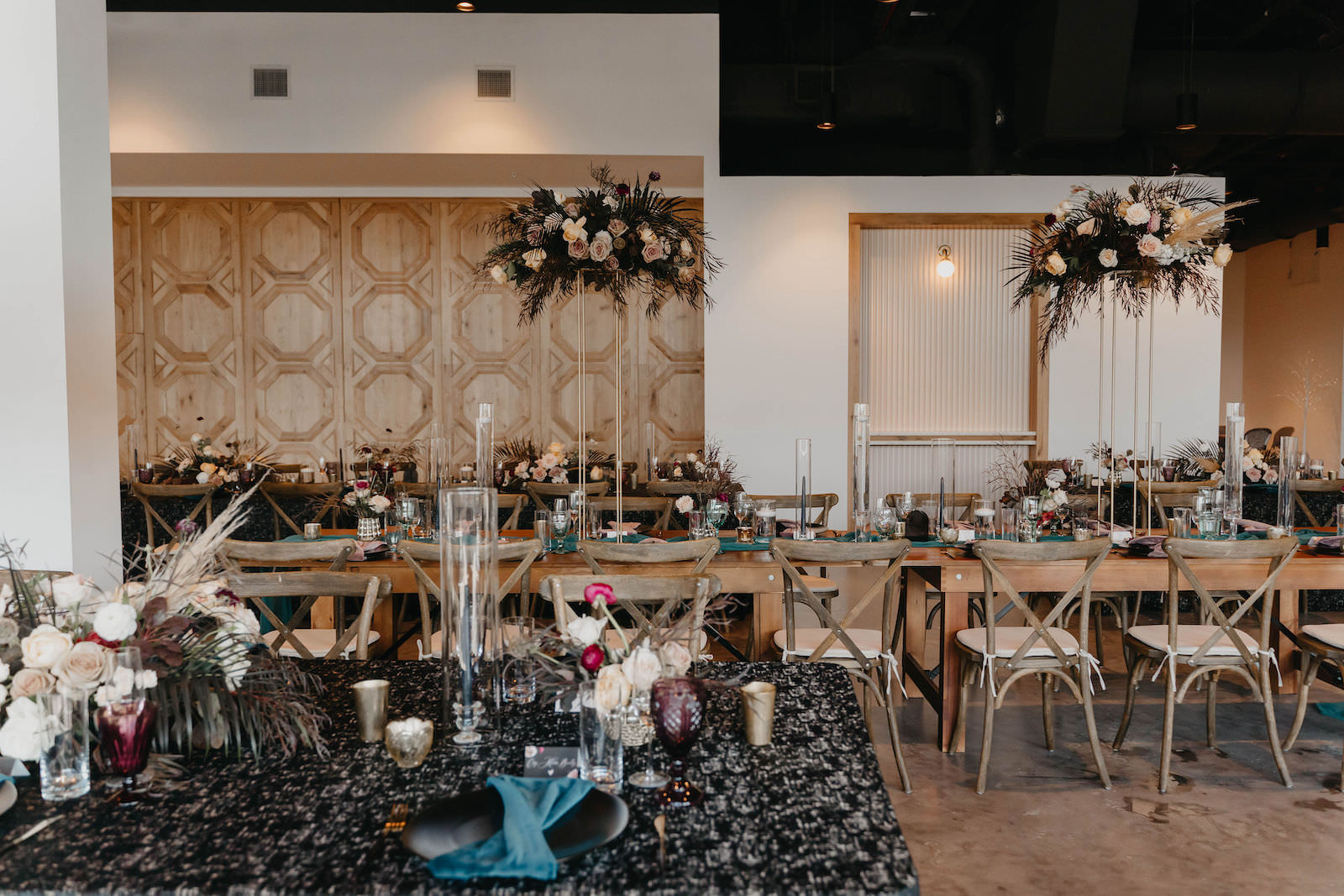 Indoor Wedding Reception at Tampa Wedding Venue Hyde House   Long Wood Feasting Communal Tables with Cross Back Chairs and Dark Emerald Green Cheesecloth Gossamer Runners and Black Sequin Tablecloth Linens   Tall Geometric Vase Centerpieces with Dark Green and Black Leaves, Pampas Grass, and Blush Cafe au Lait Roses with Candlesticks