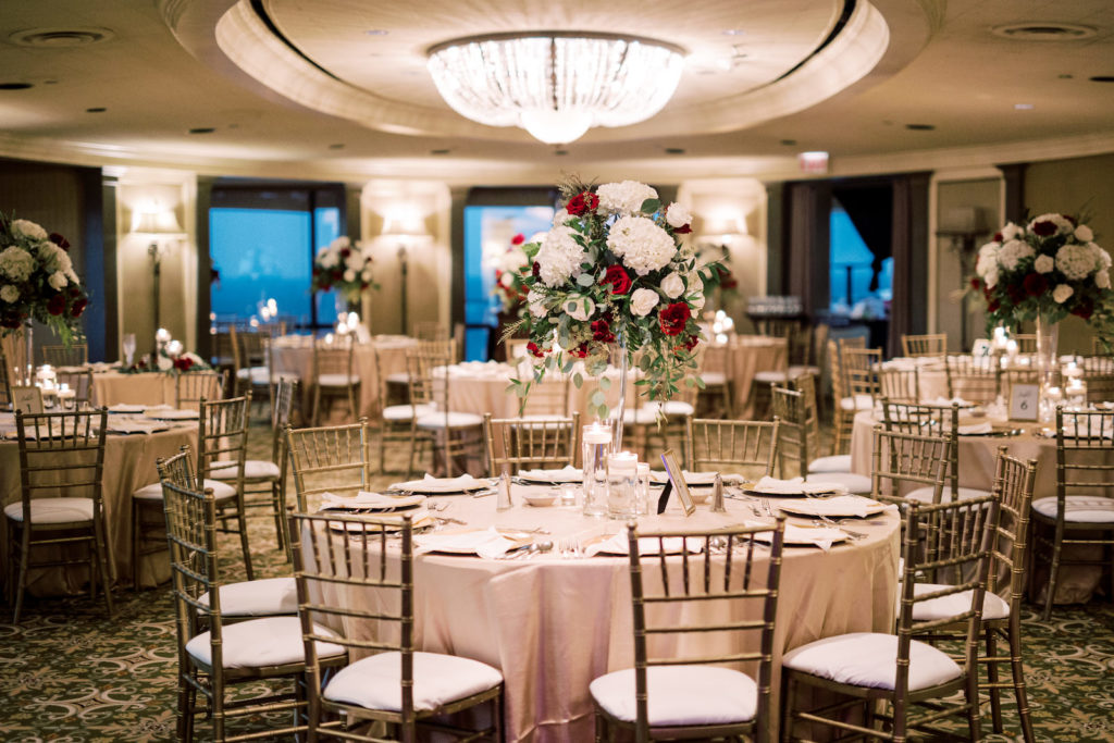 Indoor Wedding Reception at Downtown Tampa Wedding Venue The Tampa Club | Round Reception Tables with Champagne Gold Linen Tablecloths and Gold Chiavari Chairs and Gold Charger Plates | Tall Wedding Centerpieces with White Hydrangea and Red Roses and Eucalyptus Greenery with Cylinder Vase Floating Candles