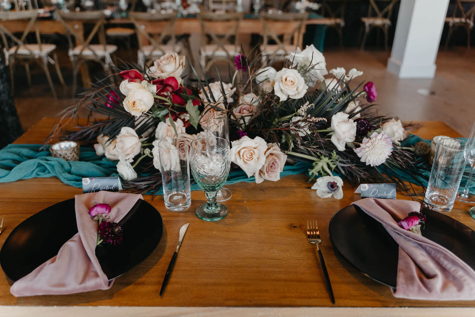 Wedding Sweetheart Table Centerpiece with Dark Emerald Green Cheesecloth Gossamer Runners and Mauve Blush Pink Velvet Napkins on Black China Plates   Low Boho Centerpieces with Dark Green and Black Leaves, Scabiosa Pods, Pink Dahlias and Ranunculus, and Blush Cafe au Lait Roses