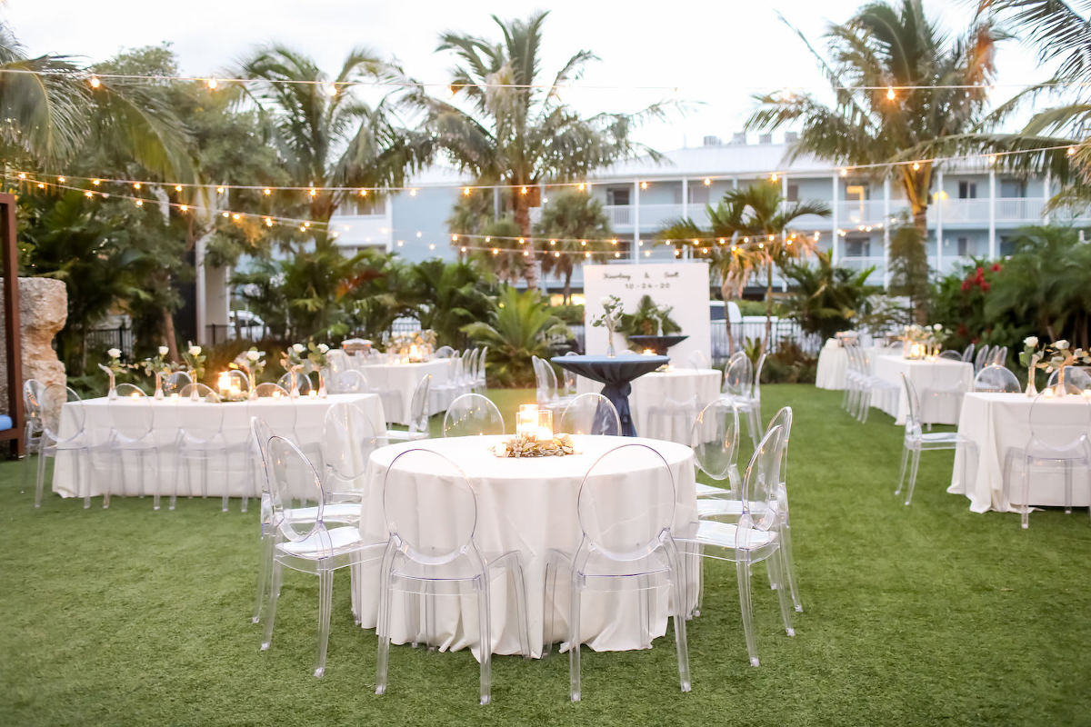Romantic, Modern Outdoor Florida Wedding Reception at Bali Hai Beachfront Resort Anna Marie Island, Long Feasting Tables and Round Tables with Acrylic Ghost Chair Rentals, Low Floral Centerpieces with Candles, Stringlighting, | Sarasota Wedding Planner Kelly Kennedy Weddings | Tampa Bay Wedding Photographer Lifelong Photography Studio