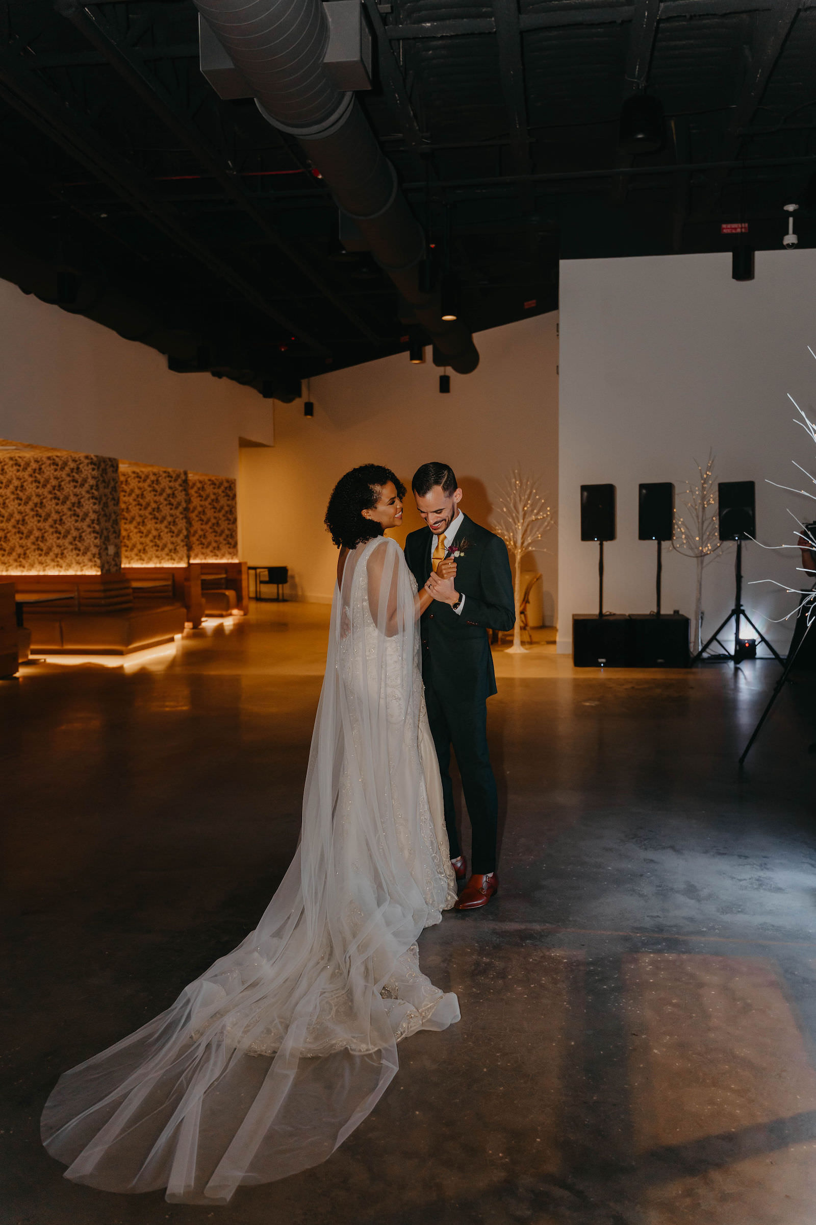 Indoor Bride and Groom First Dance in Tampa Wedding Venue Hyde House   Illusion Lace Embroidered Beaded V Neck Wedding Dress Bridal Gown with Sheer Tulle Cape Sleeves by Designer Amalia Carrara Bridal   Groom in Classic Black Tux Suit with Gold Tie