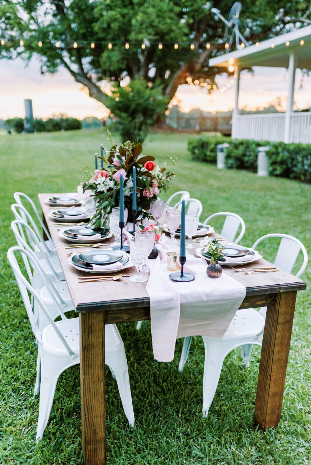 Southern Elegant Inspired Florida Outdoor Wedding Reception, Wood Table with Dark Blue Place Setting, Gold Flatware, Pink Burlap Linens, Multicolored Glass Goblets, Floral Centerpiece with Magnolia Leaves | Tampa Bay Wedding Planner EventFull Weddings | Florida Wedding Rentals Over The Top Linens | Two Sisters Ranch Dade City Florida
