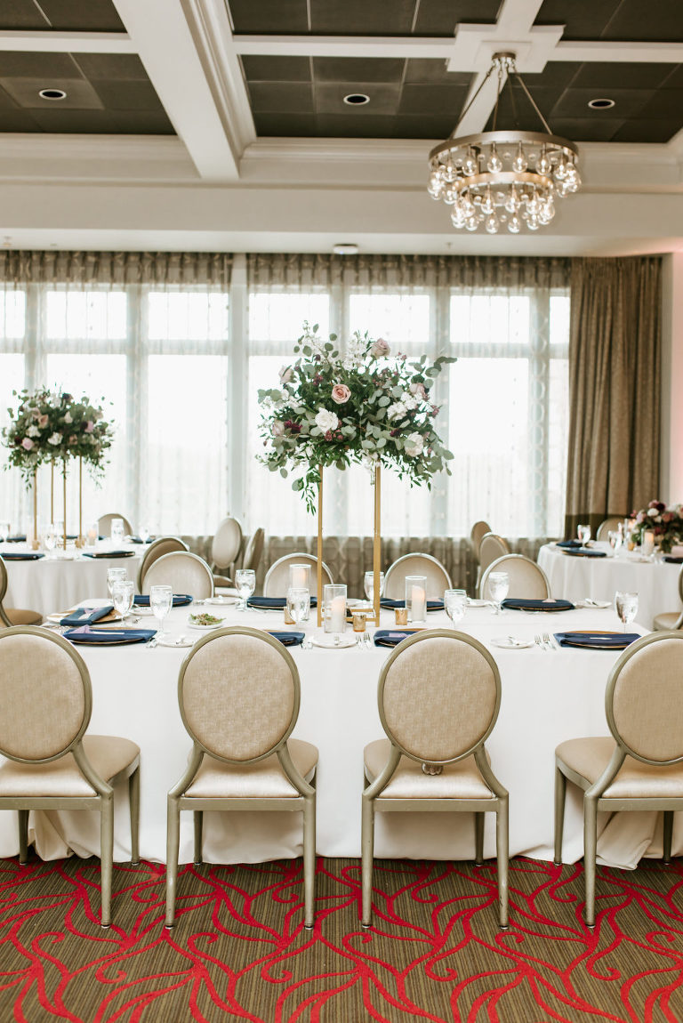 Indoor Hotel Ballroom Reception at St. Pete Wedding Venue The Birchwood | Reception Tables with Gold Banquet Chairs and Ivory Table Linens and Navy Blue Napkins | Tall Gold Metal Centerpiece Stand with Loose Natural Eucalyptus Greenery and Ivory and Pink Roses
