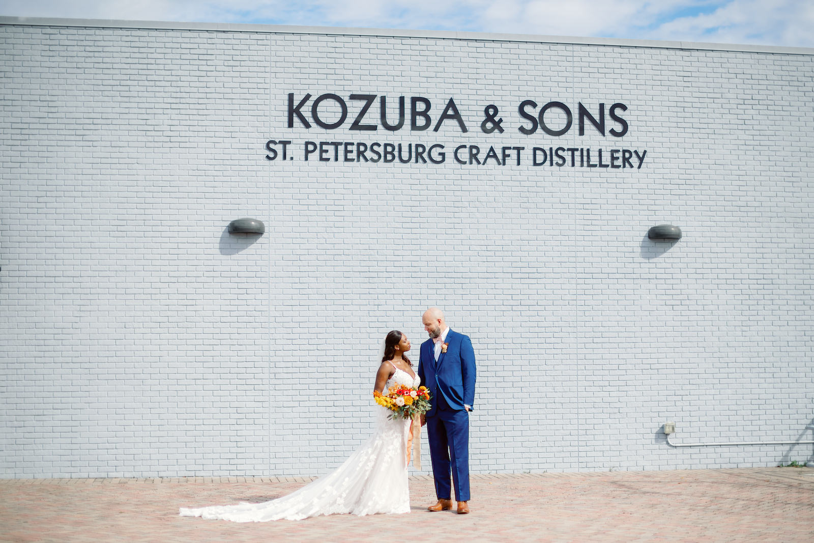 St. Petersburg Bride and Groom at Kozuba & Sons Craft Distillery, Modern Boho Florida Bride Holding Vibrant Autumn-Inspired Floral Bouquet with Orange, Yellow, Red and White Florals, Bride Wearing White Lace Mermaid Style Dress, Groom in Dark Blue Suit   Tampa Bay Wedding Planner Coastal Coordinating