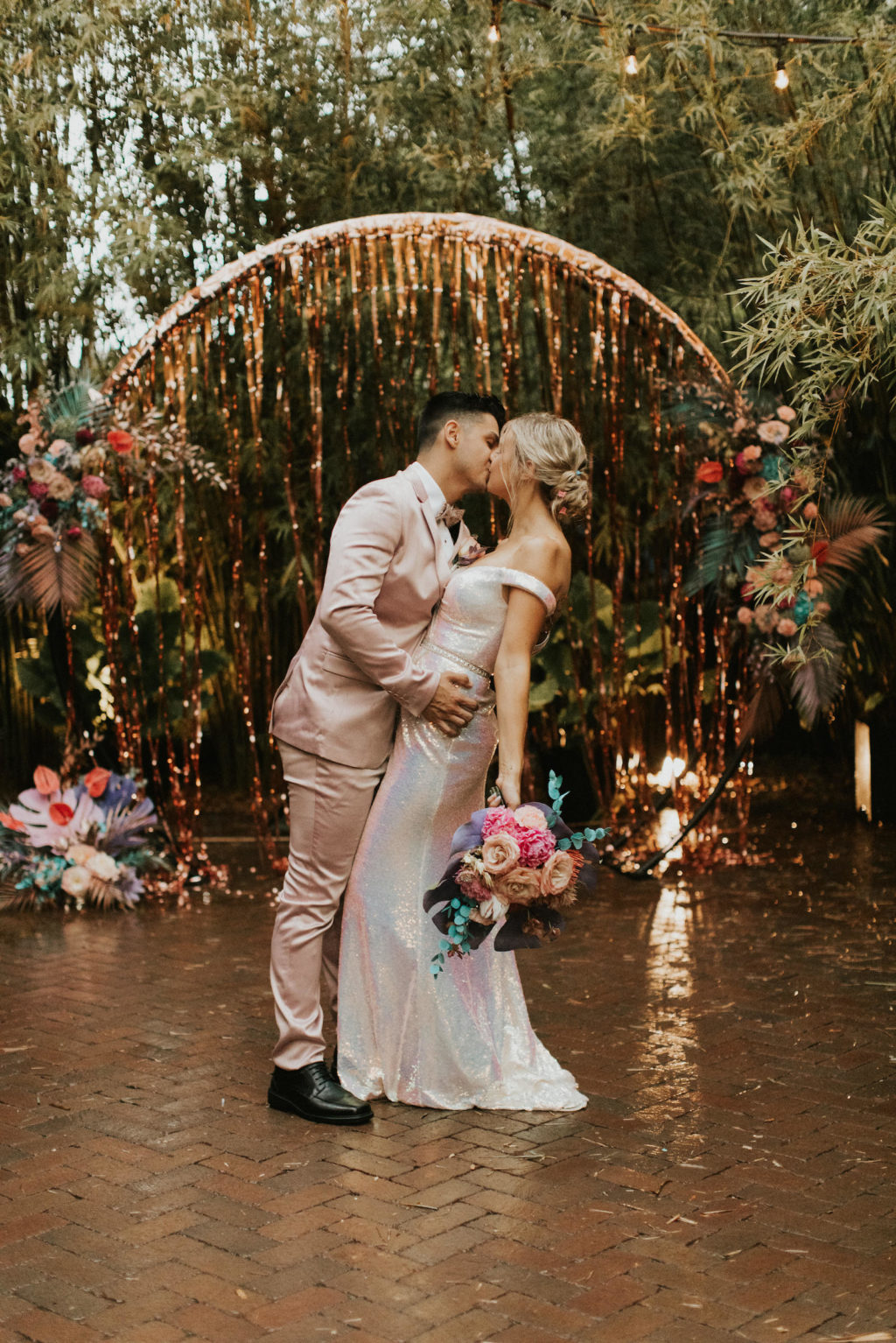 Iridescent Pastel 90's Wedding Inspiration | Wedding Arch Backdrop with Rose Gold Tinsel Curtain and Pastel Flower Arrangements with Painted Leaves | Bride and Groom Portrait with Blush Pink Suit and Shimmer Silver Wedding Dress | Downtown St. Pete Wedding Venue NOVA 535