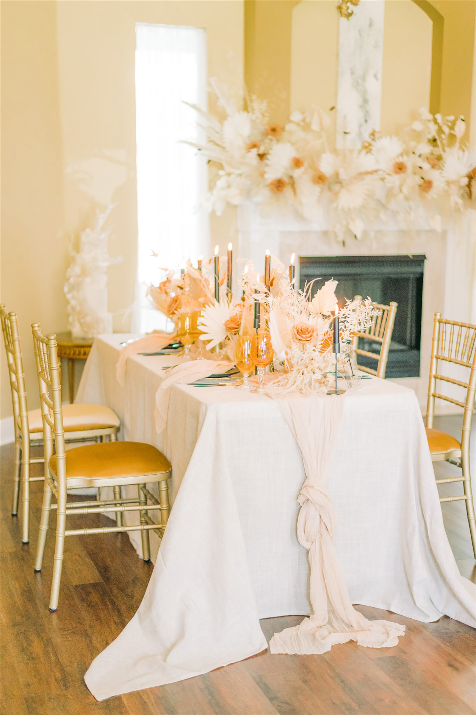 Trendy and Modern Boho Wedding Reception Decor, Long Table with White Tablecloth, Gold Chiavari Chairs with Beige Cushions, White Floral Preserved Flowers and Foliage, Ivory Table Runner, Candlesticks | Tampa Bay Wedding Planner, Designer, Florist John Campbell Weddings | Tabletop Rentals Kate Ryan Event Rentals