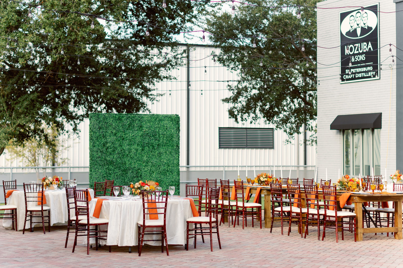 Boho Inspired Florida Wedding Reception and Decor, Autumn Wedding Theme with Warm Color Palette, Dark Red Chiavari Rental chairs, Round Tables with White Tablecloths and Burnt Orange Linens, Low Floral Centerpieces with Yellow Crystal Goblets, Greenery Boxwood Wall   Kozuba & Sons St. Petersburg Craft Distillery   Tampa Bay Wedding Planner Coastal Coordinating