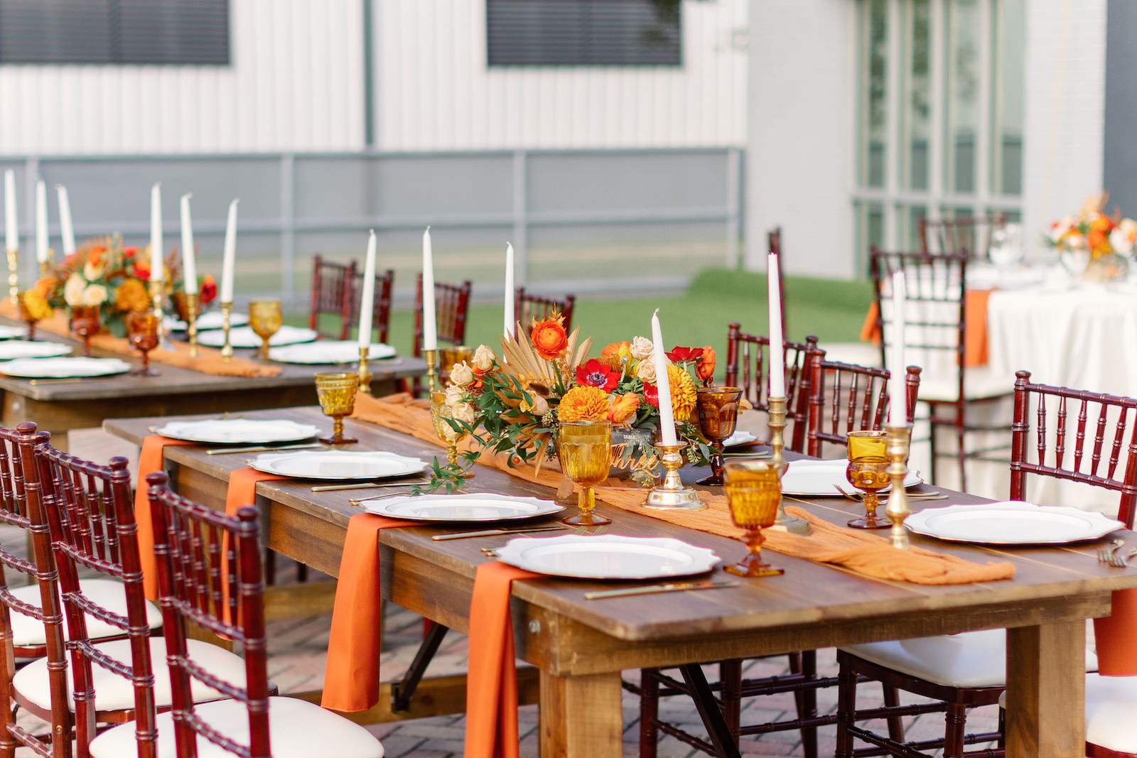 Modern Boho Inspired Florida Wedding Reception and Decor   Long Wooden Feasting Table with Burnt Orange Linen Table Runner with Long White Candles and Gold Candleholder, White Chargers, Orange, Golden Yellow and Red Floral Centerpiece   Tampa Bay Wedding Planner Coastal Coordinating