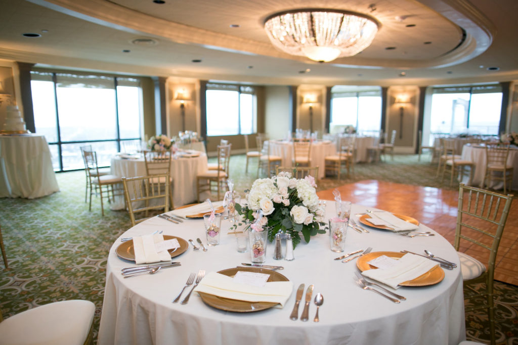 Indoor Wedding Reception at Downtown Tampa wedding Venue The Tampa Club | White Reception Table Linens with Gold Chiavari Chairs and Chargers and Centerpieces of White Hydrangea and White and Blush Pink Roses with Eucalyptus Greenery | Pint Glass Wedding Favors | Carrie Wildes Photography