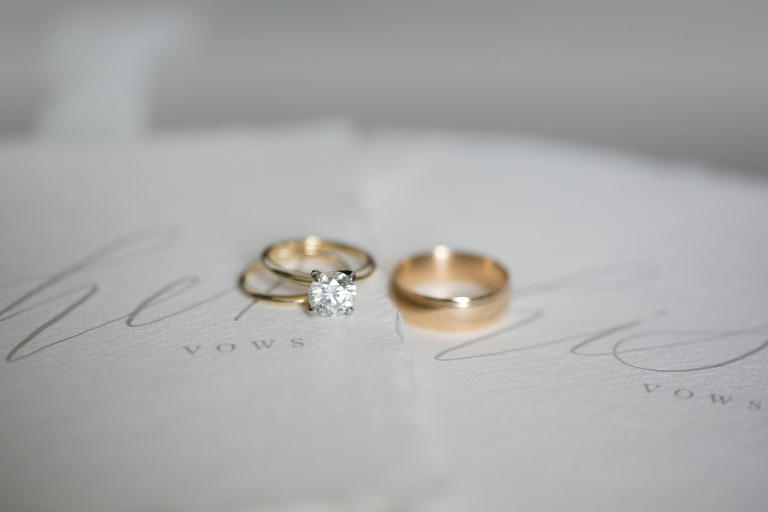 wedding ring photo shot | Yellow gold mens band and round Tiffany style diamond solitaire engagement ring