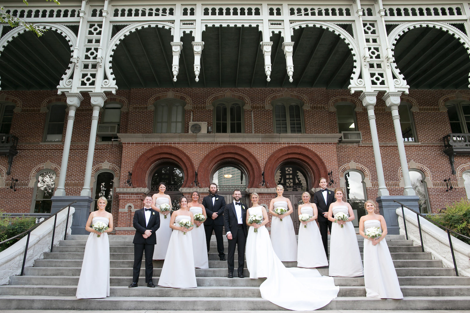 Wedding Party Outdoor Portrait in Downtown Tampa at Plant Museum UT | Bateau Neck Mikado Satin Martina Liana Simple Elegant Wedding Dress with Buttons Down Back | Groom and Groomsmen in Classic Black Tux | Neutral White Rose and Greenery Bouquets | Strapless Taupe Neutral Bridesmaid Dresses by Amsale | Carrie Wildes Photography