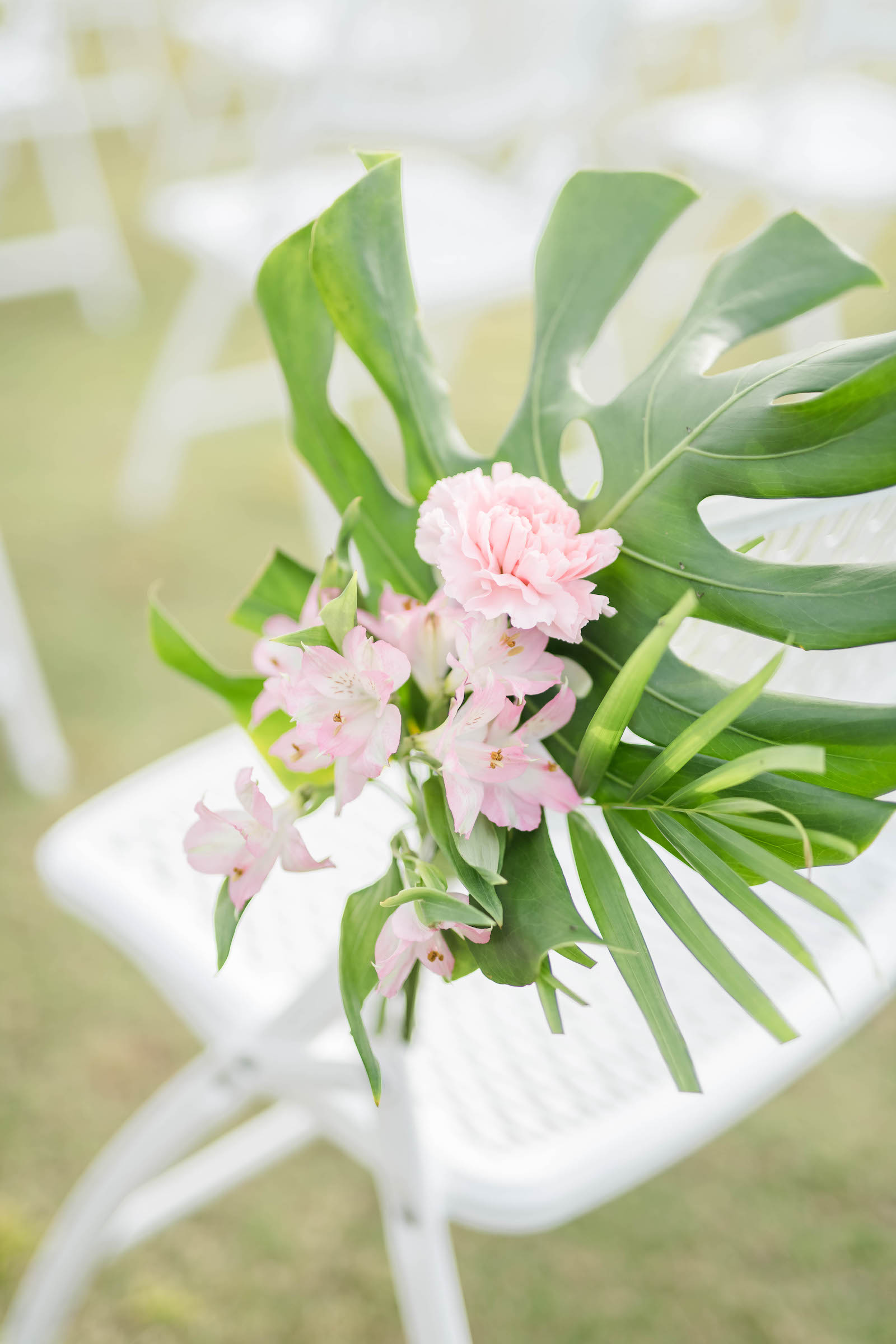 Tropical Wedding Ceremony Decor, Monstera Leaves and Palm Fronds, Pink Flowers Arrangement on Chairs | Tampa Bay Wedding Planner Coastal Coordinating