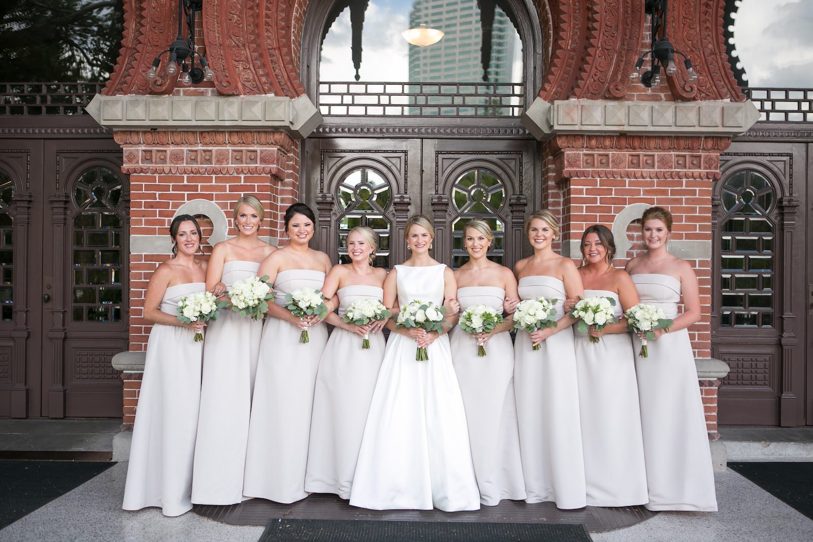 Bridal Party Outdoor Portrait in Downtown Tampa at Plant Museum UT | Bateau Neck Mikado Satin Martina Liana Simple Elegant Wedding Dress with Buttons Down Back | Neutral White Rose and Greenery Bouquets | Strapless Taupe Neutral Bridesmaid Dresses by Amsale | Carrie Wildes Photography