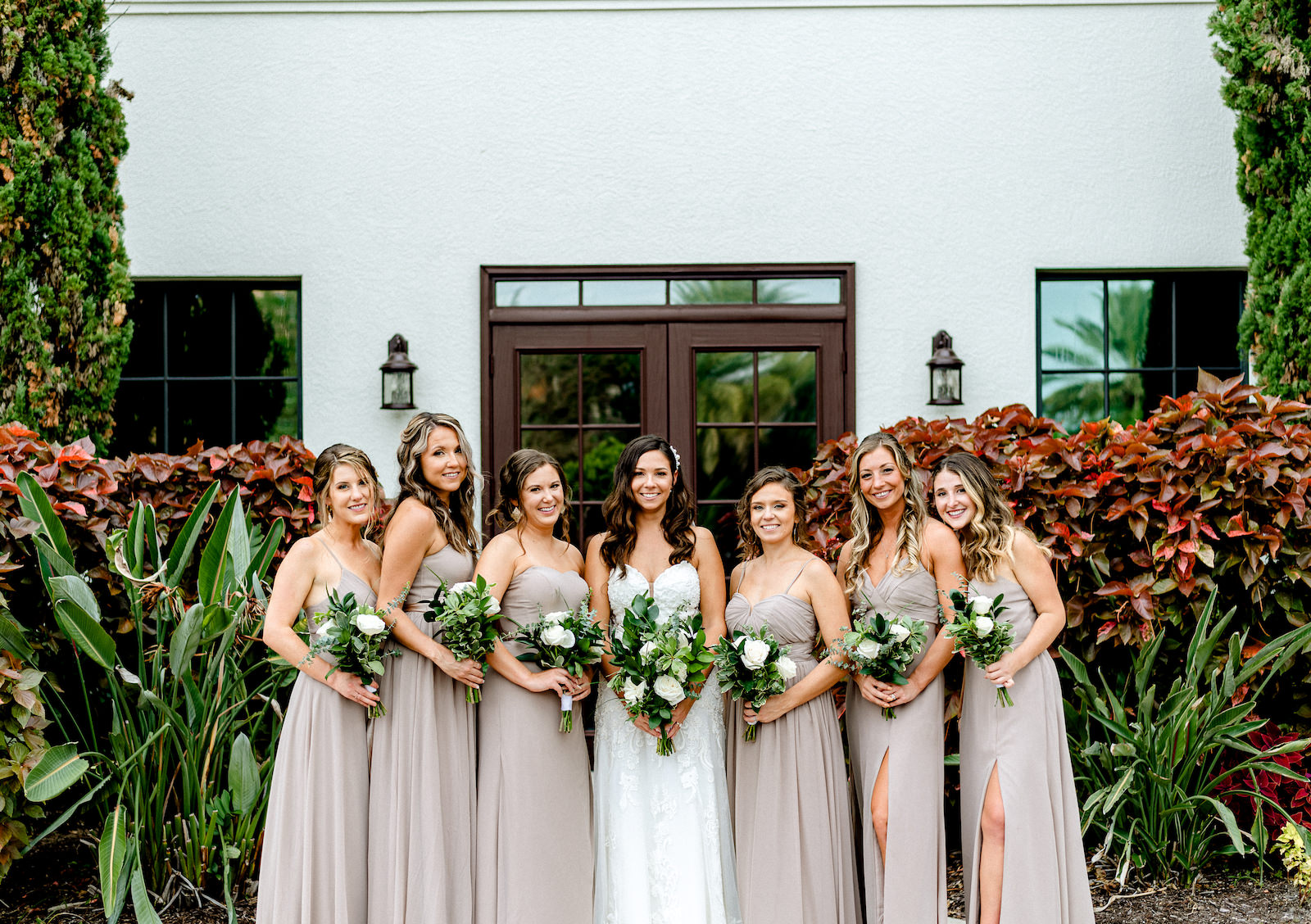 Bridal Party Outdoor Portrait at Tampa wedding Venue Westshore Yacht Club | Lace Strapless Sweetheart Scalloped Edge Train Wedding Dress Bridal Gown | Bridesmaid Bouquets with Greenery and white Roses | Long Chiffon Taupe Champagne Neutral Bridesmaid Dresses by Lulu's | Dewitt for Love Photography