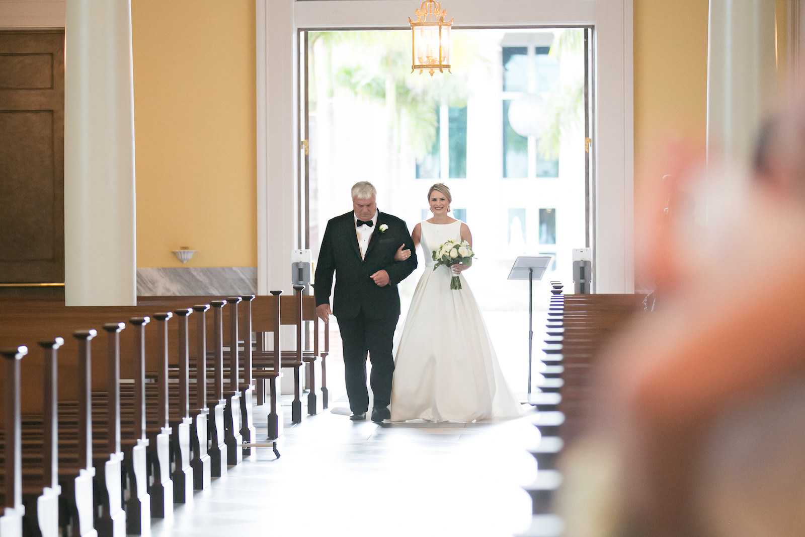 Bride Walking down Aisle with Father during Traditional Church Wedding Ceremony in Tampa | Bateau Neck Mikado Satin Martina Liana Simple Elegant Wedding Dress with Buttons Down Back | Neutral White Rose and Greenery Bouquet