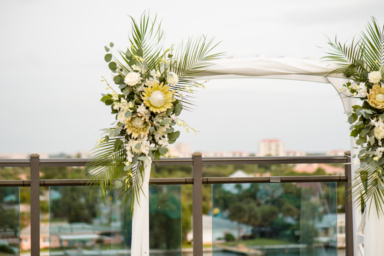 Neutral Boho Tropical Wedding Ceremony Decor, Lush Floral Arrangement on Arch, King Proteas, White Roses and Orchids, Palm Fronds, Eucalyptus | Tampa Bay Wedding Planner Perfecting the Plan | Waterfront St. Pete Wedding Venue The Hotel Zamora | Wedding Florist Iza's Flowers