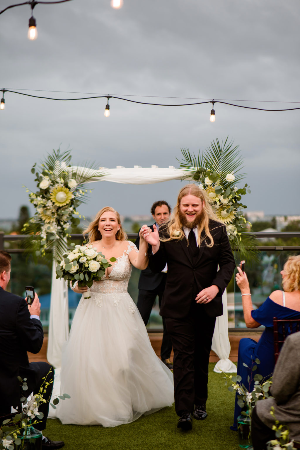Florida Bride and Groom Wedding Ceremony Exit, Boho Neutral Tropical Wedding Ceremony Decor, Arch with Lush Floral Arrangements, Eucalyptus, King Proteas, White Florals and Palm Fronds | Tampa Bay Wedding Planner Perfecting the Plan | Wedding Florals Iza's Flowers
