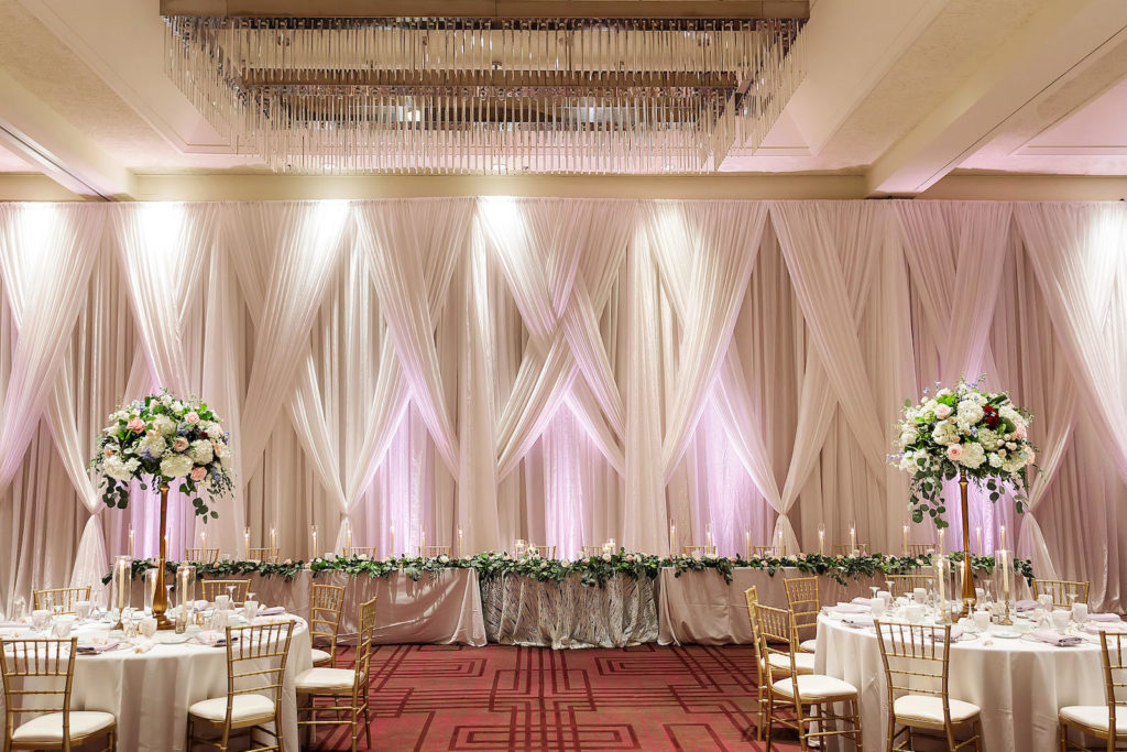 Tampa Hotel Wedding Reception at Hilton Downtown Tampa Ballroom | Long Feasting Head Table with Greenery Garland and Taper Candles | White Table Linens with Gold Chiavari Chairs and Tall Gold Centerpieces of White Hydrangea, Blush Pink and Deep Red Roses and Dusty Blue Eucalyptus Greenery by Tampa Wedding Florist Monarch Events and Design | White Pipe and Drape Room Divider Wall with LED Uplighting