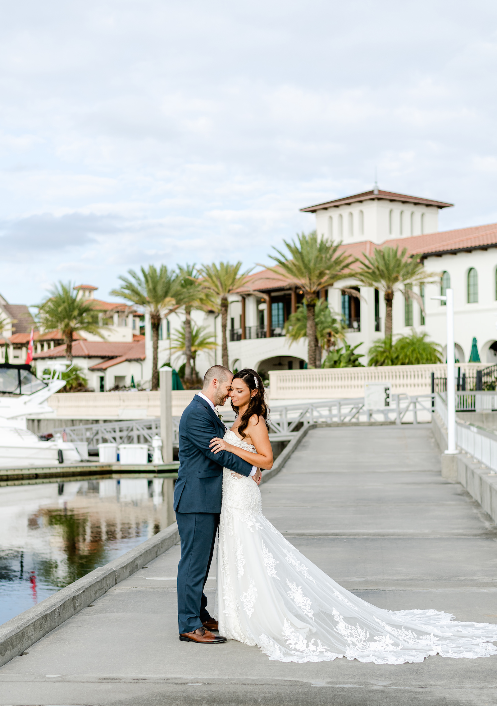 Bride and Groom Outdoor Portrait along Marina Dock at Tampa wedding venue westshore Yacht Club | Lace Strapless Sweetheart Scalloped Edge Train Wedding Dress Bridal Gown | Groom Wearing Classic Navy Suit | Dewitt for Love Photography