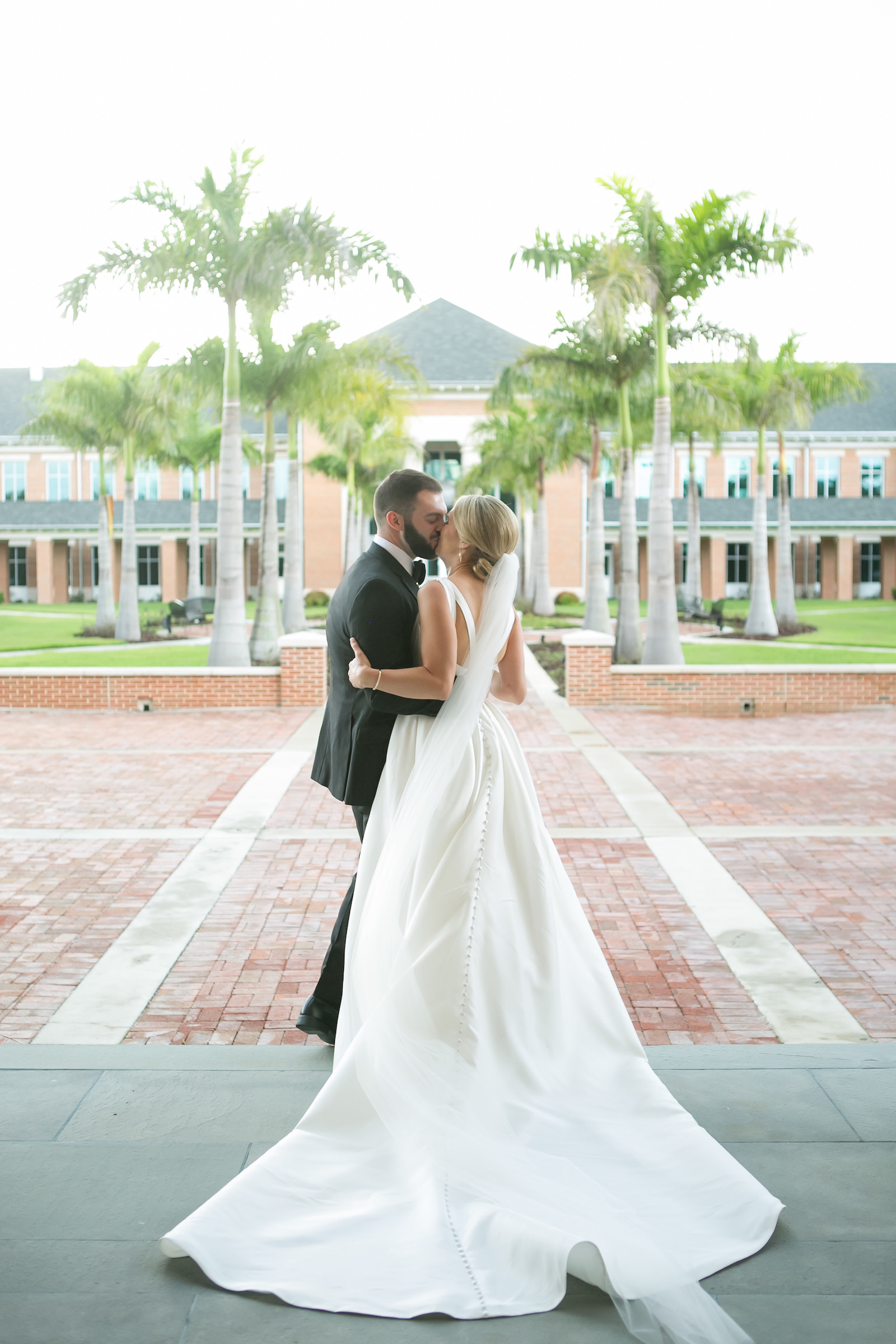 Bride and Groom Outdoor Portrait | Bateau Neck Mikado Satin Martina Liana Simple Elegant Wedding Dress with Buttons Down Back | Groom in Classic Black Tux