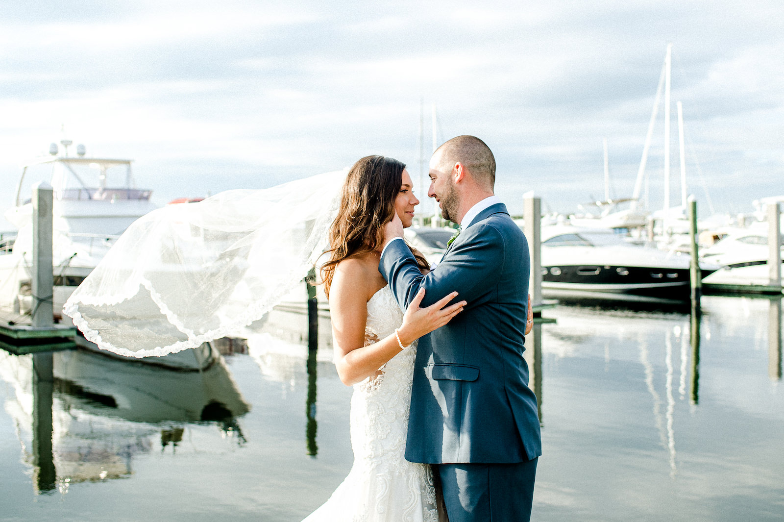 Bride and Groom Outdoor Portrait along Marina Dock at Tampa wedding venue Westshore Yacht Club | Lace Strapless Sweetheart Scalloped Edge Train Wedding Dress Bridal Gown with Elbow Length Lace Edge Veil | Groom Wearing Classic Navy Suit | Dewitt for Love Photography