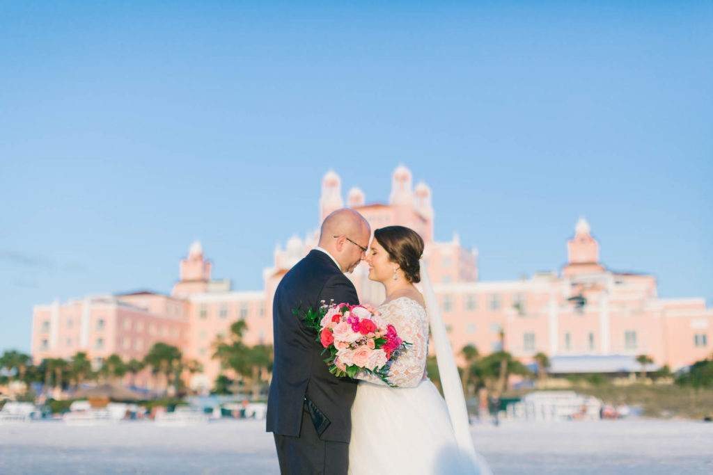 Florida Bride and Groom on Beach with Vibrant Pink Floral Bouquet | Historic Downtown St. Pete Wedding Venue The Don Cesar | Tampa Bay Wedding Florist Bruce Wayne Florals