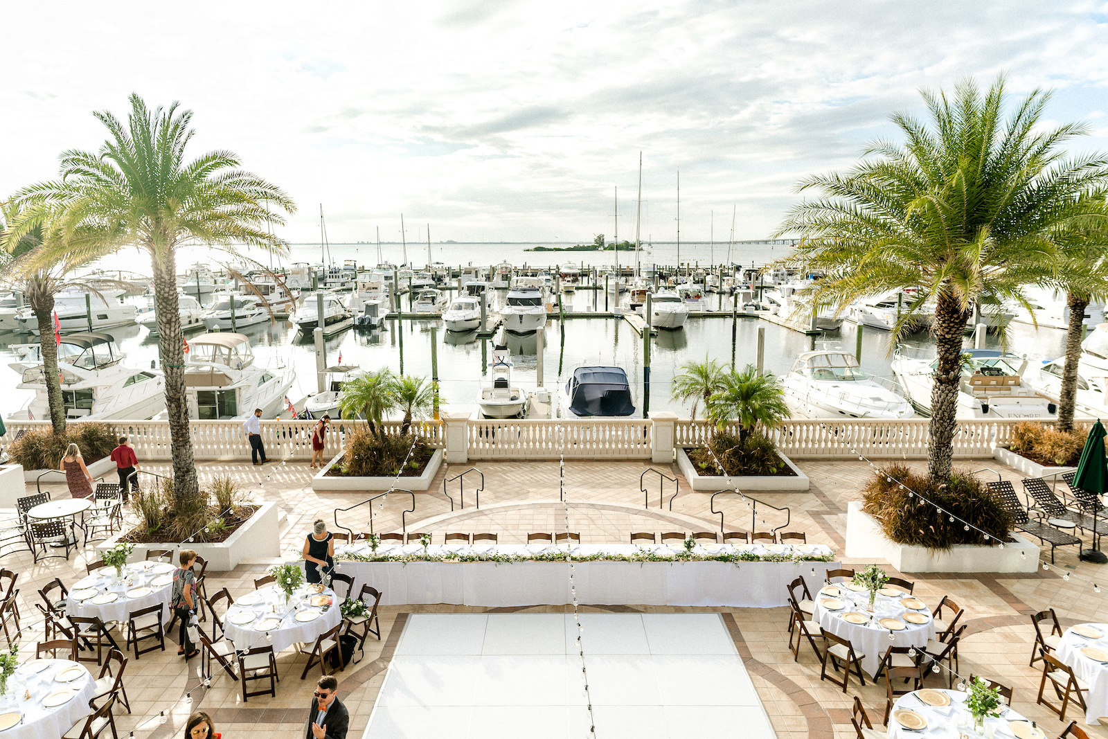 Outdoor wedding Reception at Tampa wedding Venue westshore Yacht Club | Round tables with white linens and mahogany wood folding chairs with gold charger plates and greenery centerpieces | long wedding head table with white dance floor